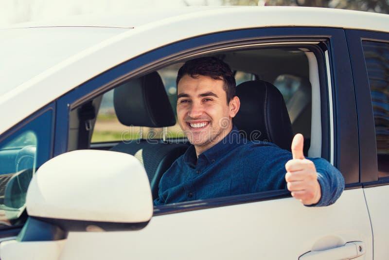 Stående av den lyckliga grabben, tumme för uberchaufförvisning upp den positiva gesten som försiktigt ler till kameran arkivfoton