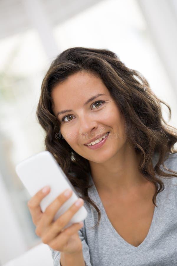 Stående av den lyckliga gulliga kvinnan med mobiltelefonsammanträde på soffan royaltyfri bild