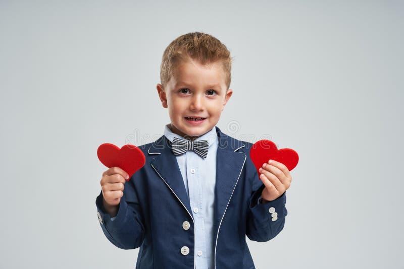Stående av den lyckliga gulliga lilla ungen som rymmer röd hjärta arkivfoton