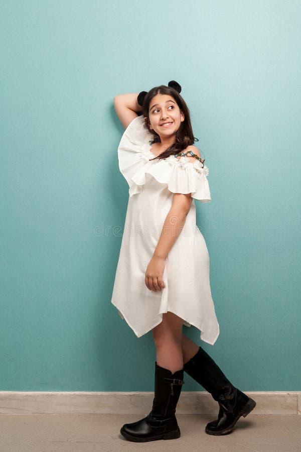Stående av den lyckliga härliga brunettunga flickan med svart långt rakt hår i den vita klänningen som bort står, poserar och ser arkivfoto