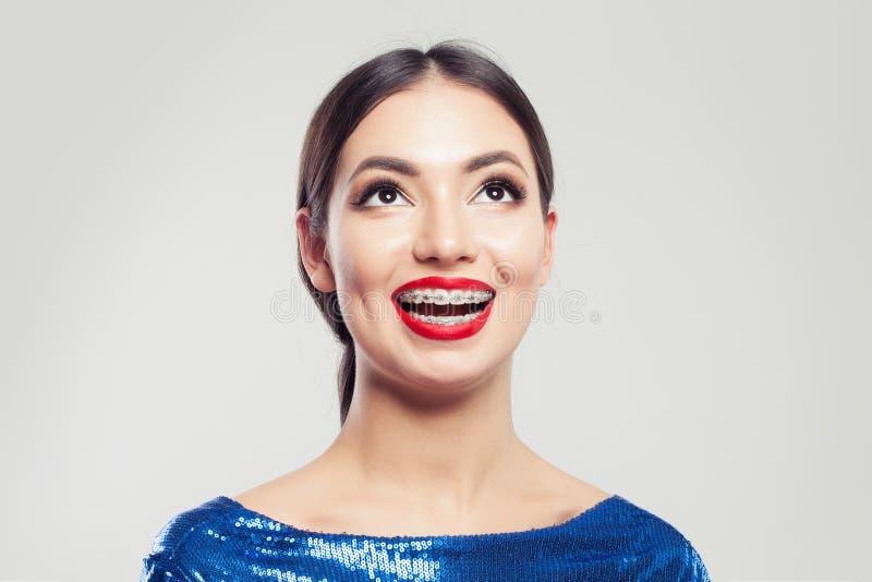 Stående av den lyckliga härliga kvinnan i hänglsen på vit bakgrund Nätt flicka med hänglsen på att le för tänder arkivbild