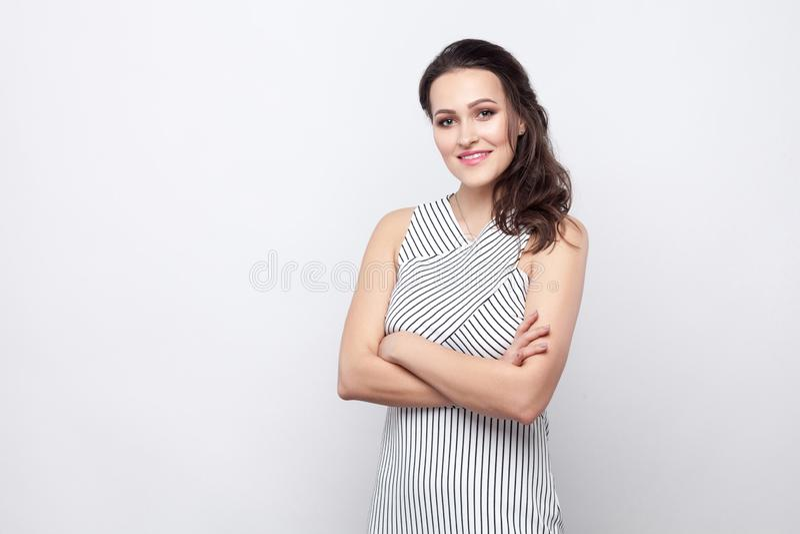 Stående av den lyckliga härliga unga brunettkvinnan med makeup och det randiga klänninganseendet med korsade armar och att se kam royaltyfri bild