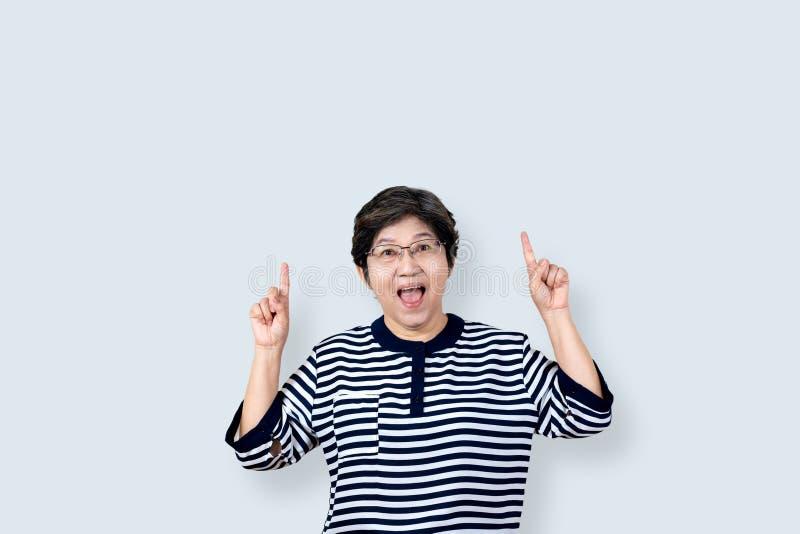Stående av den lyckliga höga asiatiska gesten eller att peka handen upp och fingret och att se för kvinna kameran på isolerad bak fotografering för bildbyråer