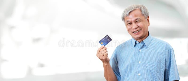 Stående av den lyckliga höga asiatiska maninnehavkreditkorten och uppvisning förestående av att le och av att se kameran på isole fotografering för bildbyråer
