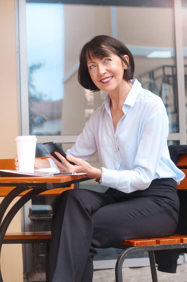 Stående av den lyckliga höga kvinnan som sitter på kafét genom att använda mobiltelefonen arkivfoto