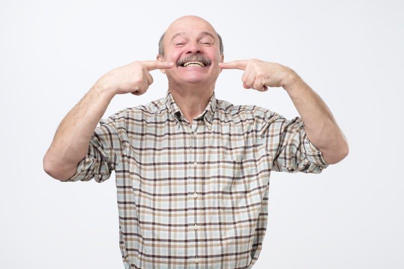 Stående av den lyckliga höga le mannen som pekar på hans tänder med fingrar arkivbild