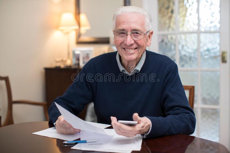 Stående av den lyckliga höga mannen som granskar hemhjälpfinanser arkivfoton