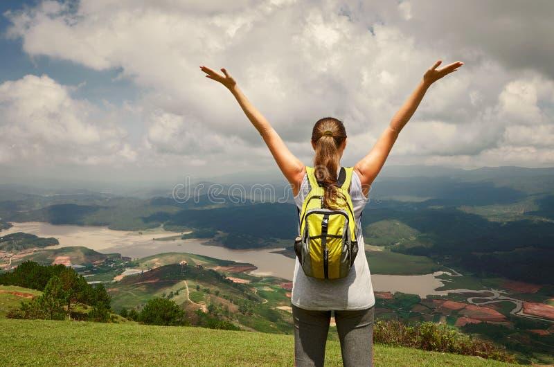 Stående av den lyckliga handelsresandekvinnan med ryggsäcken som överst står nolla arkivbild