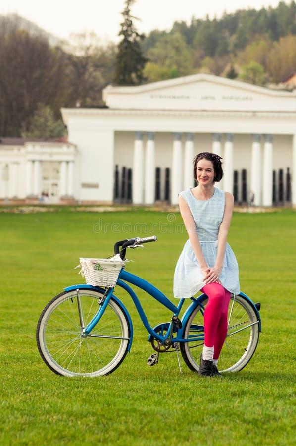 Stående av den lyckliga hipsterkvinnan som tycker om våren på en cykel arkivbilder