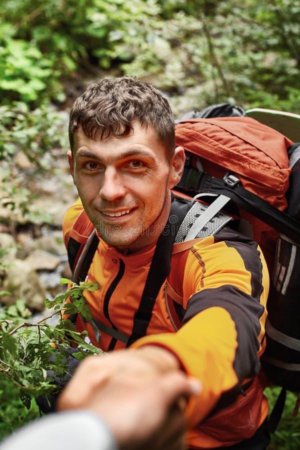Stående av den lyckliga innehavhanden för ung man av hans vän, medan gå vid berget, selektiv fokus royaltyfri bild