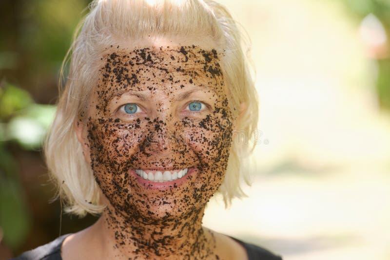 Stående av den lyckliga kvinnan med en pilling maskering för kaffe royaltyfri bild