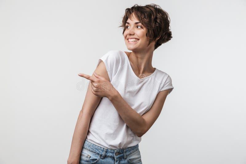 Stående av den lyckliga kvinnan med kort hår i grundläggande t-skjorta fröjd och pekafingret på copyspace royaltyfria bilder