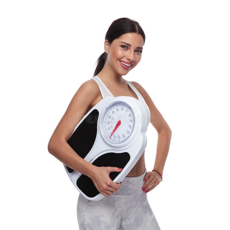 Stående av den lyckliga kvinnan med skalan som främjar en sund livsstil royaltyfri foto
