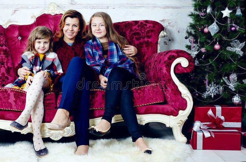 Stående av den lyckliga kvinnan med två döttrar som sitter på soffan arkivbilder
