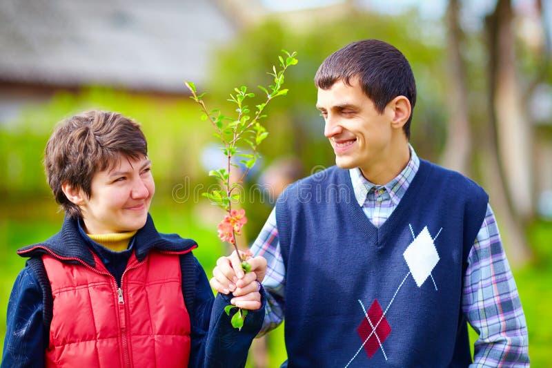 Stående av den lyckliga kvinnan och mannen med handikapp tillsammans på vårgräsmatta royaltyfri bild