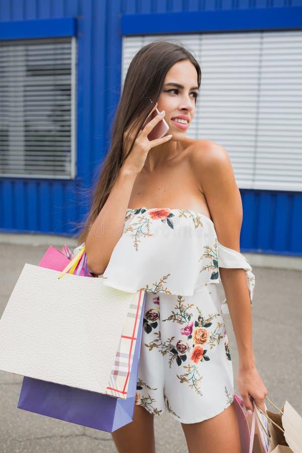 Stående av den lyckliga kvinnliga köparen med shoppingpåsar Dam som förutom bär så många shoppingpåsar klädlagret royaltyfria bilder