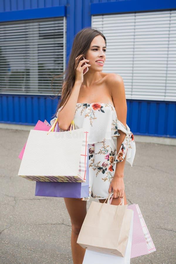 Stående av den lyckliga kvinnliga köparen med shoppingpåsar Dam som förutom bär så många shoppingpåsar klädlagret royaltyfri bild
