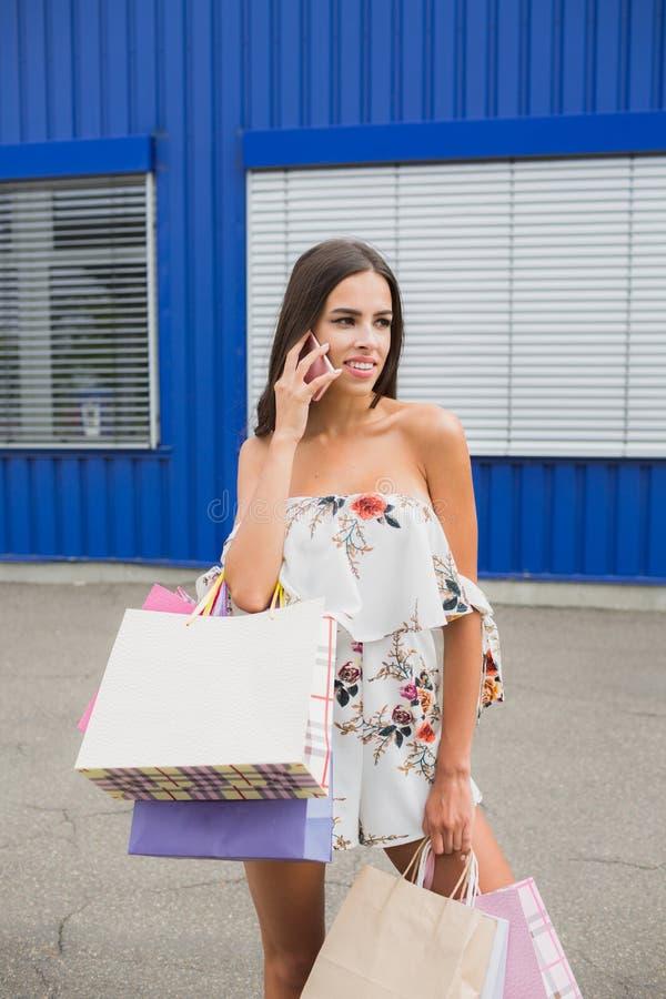 Stående av den lyckliga kvinnliga köparen med shoppingpåsar Dam som förutom bär så många shoppingpåsar klädlagret arkivfoton