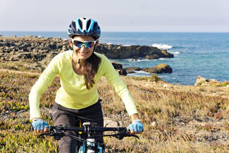 Stående av den lyckliga kvinnliga turist- cyklistridningmountainbiket royaltyfria foton