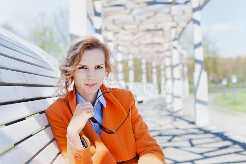 Stående av den lyckliga le affärskvinnan eller modestudenten med solglasögon som sitter på den utomhus- bänken arkivfoton