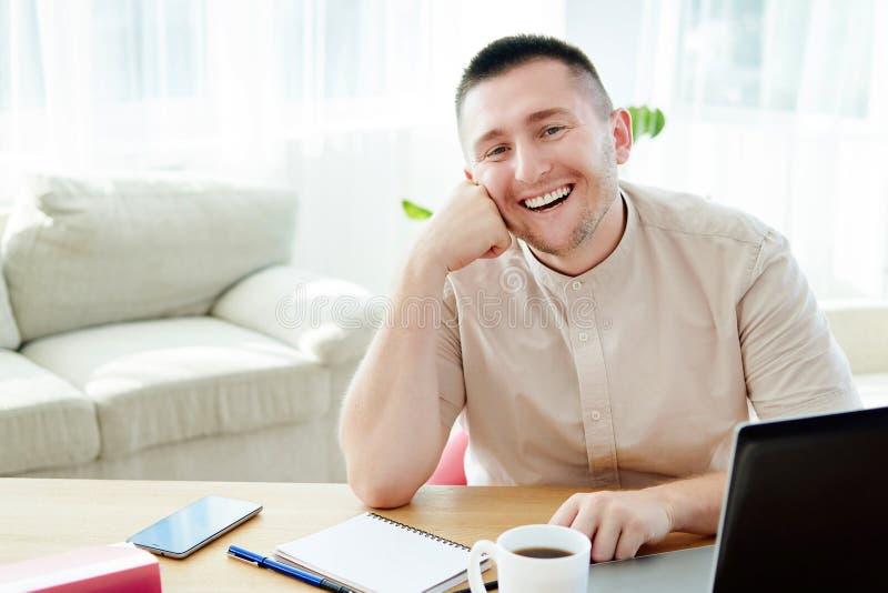 Stående av den lyckliga le affärsmannen som sitter på träskrivbordet med notepat- och bärbar datordatoren i modernt kontor och se arkivbilder