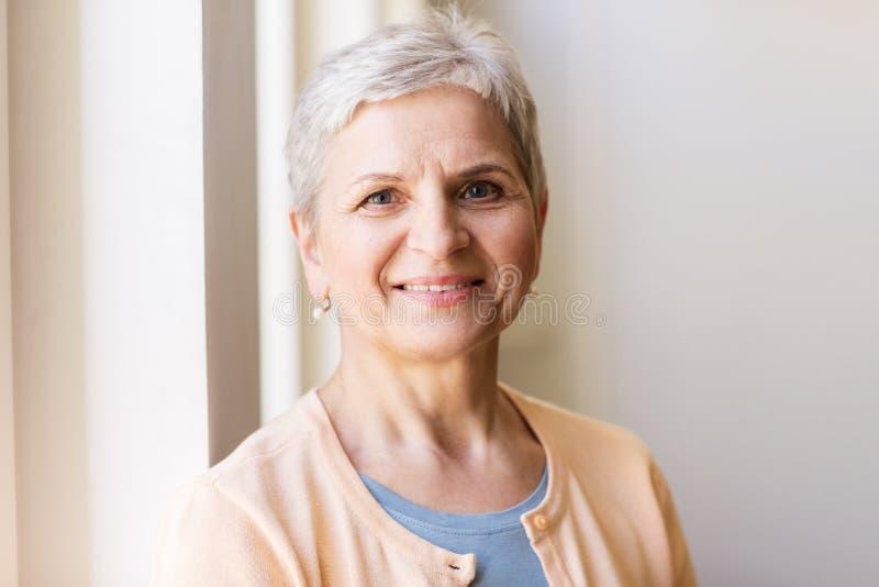 Stående av den lyckliga le gråa höga kvinnan arkivfoton