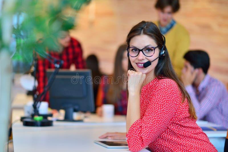 Stående av den lyckliga le kvinnliga operatören för telefon för kundservice på arbetsplatsen arkivbilder