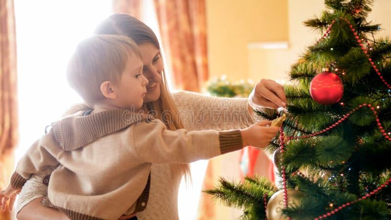 Stående av den lyckliga le modern med hennes decroating julgran för barn på morgonen royaltyfri foto