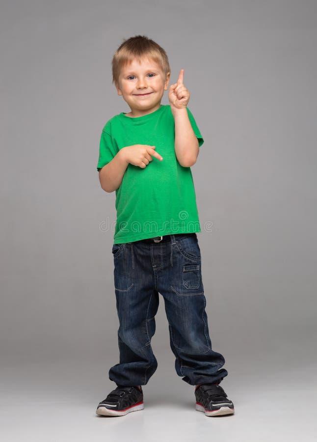 Stående av den lyckliga le pojken i grön t-skjorta och jeans Attraktiv unge i studio royaltyfria bilder