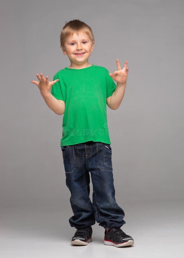 Stående av den lyckliga le pojken i grön t-skjorta och jeans Attraktiv unge i studio arkivfoton