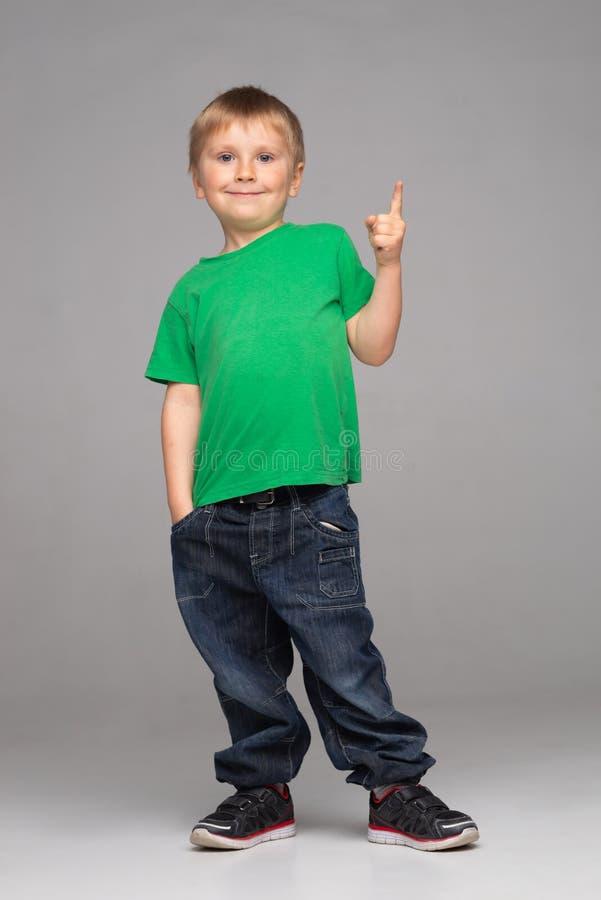 Stående av den lyckliga le pojken i grön t-skjorta och jeans Attraktiv unge i studio fotografering för bildbyråer