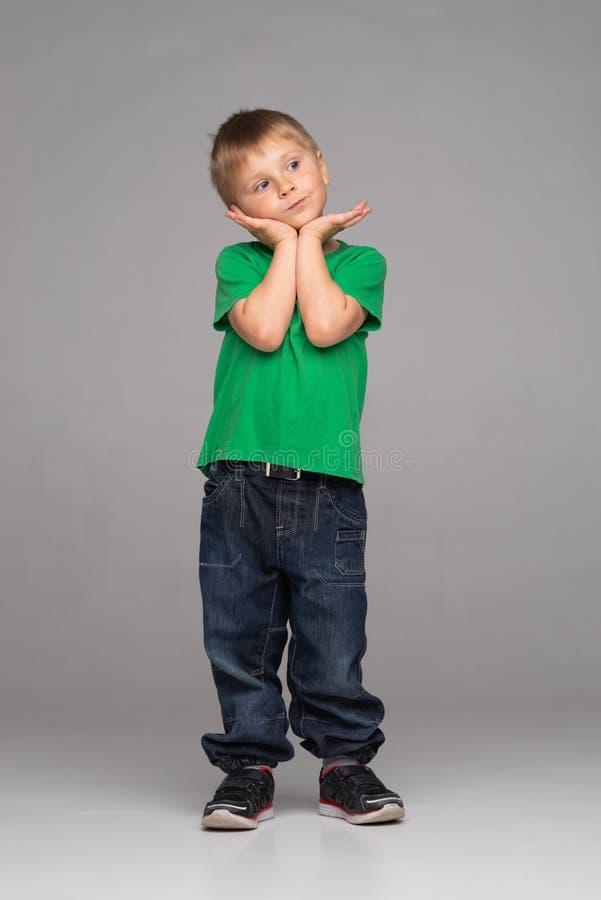 Stående av den lyckliga le pojken i grön t-skjorta och jeans Attraktiv unge i studio arkivbilder