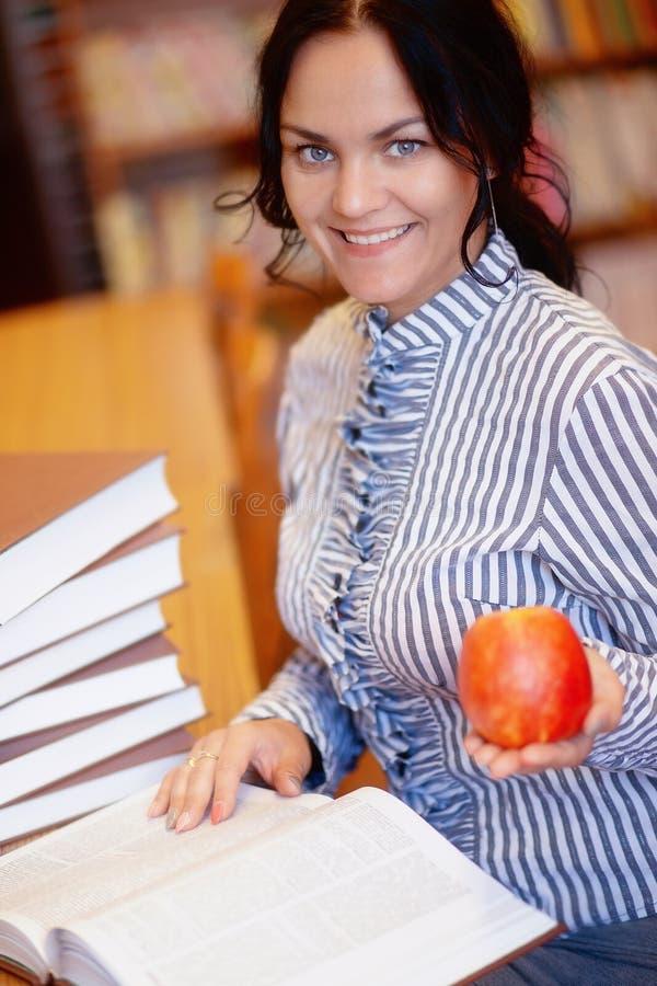 Stående av den lyckliga le unga brunettstudentflickan med äpplet royaltyfri fotografi
