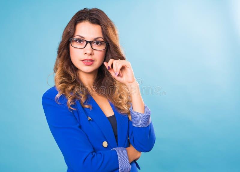 Stående av den lyckliga le unga gladlynta affärskvinnan i exponeringsglas över blå bakgrund Caucasian brunettmodell in arkivbild