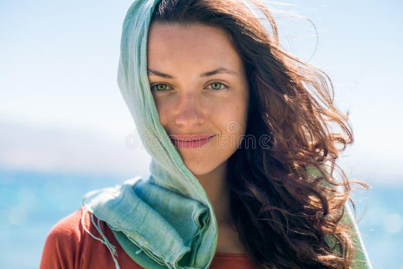 Stående av den lyckliga le unga kvinnan med den långa hår och gräsplanhalsduken på strand- och havsbakgrunden royaltyfri foto