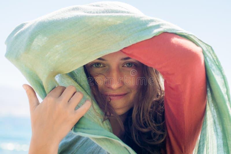 Stående av den lyckliga le unga kvinnan med långt hår Hon döljer och skapar en skugga med halsduken royaltyfri foto