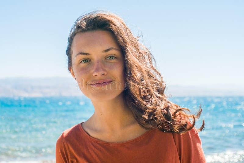 Stående av den lyckliga le unga kvinnan med långt hår på strand- och havsbakgrunden royaltyfri fotografi