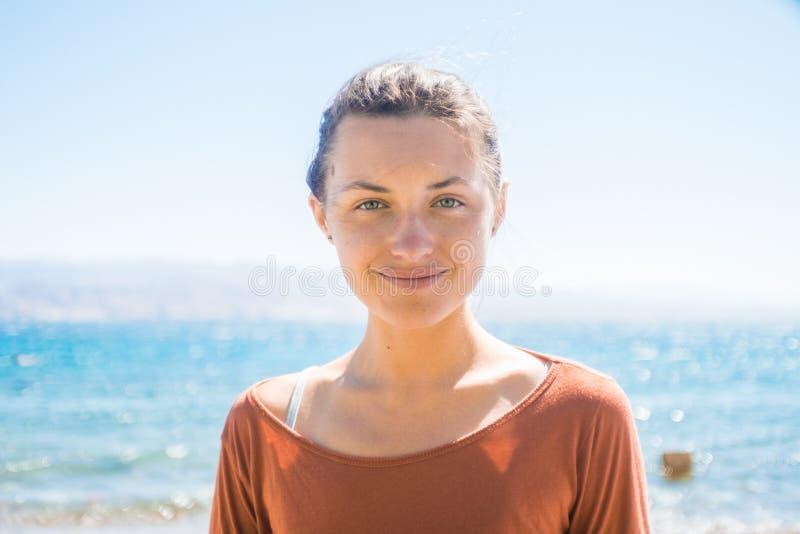 Stående av den lyckliga le unga kvinnan på stranden med havsbakgrund arkivbild