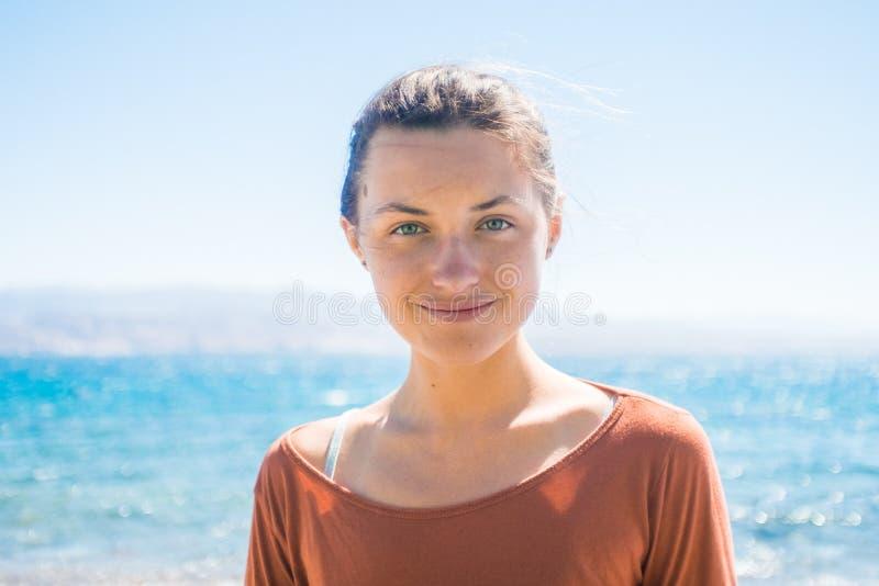 Stående av den lyckliga le unga kvinnan på stranden med havsbakgrund arkivfoto