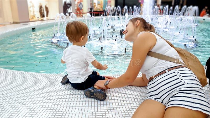 Stående av den lyckliga le unga modern med det lilla barnet som sitter i shoppinggalleria och ser på den härliga springbrunnen fotografering för bildbyråer