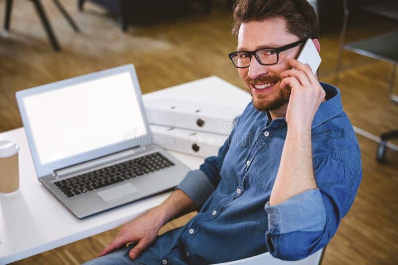 Stående av den lyckliga ledaren som talar på mobiltelefonen på det idérika kontoret arkivfoto