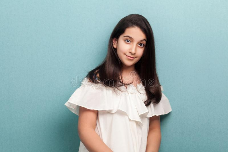 Stående av den lyckliga lugna härliga brunettunga flickan med svart långt rakt hår, i det vita anseendet och att se för klänning  arkivbilder