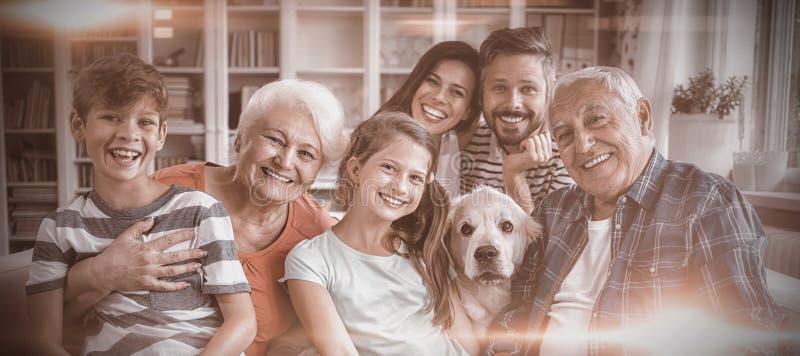 Stående av den lyckliga mång- utvecklingsfamiljen som sitter på soffan i vardagsrum royaltyfria bilder