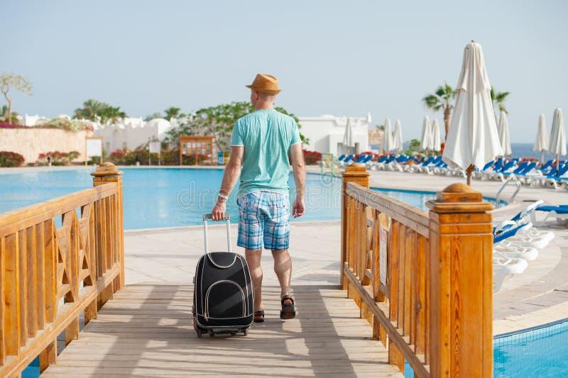 Stående av den lyckliga mannen med resväskaanseende nära pöl Begrepp av turism och att koppla av för lopp arkivfoton