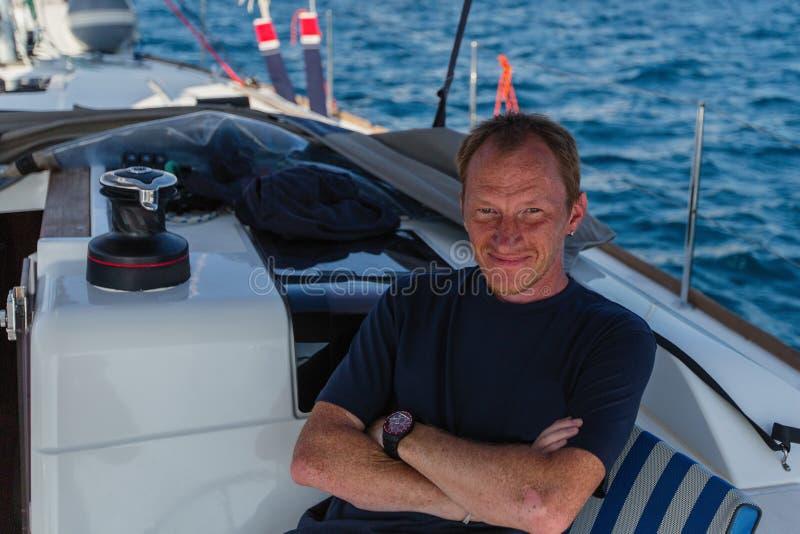 Stående av den lyckliga mannen på hans segla yachtfartyg på havet Sommar royaltyfri bild