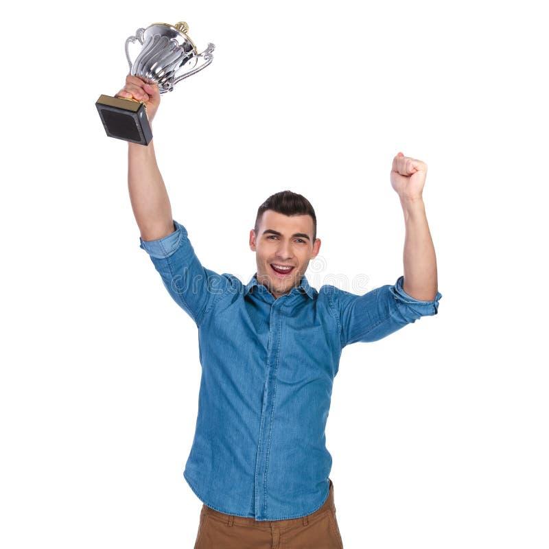 Stående av den lyckliga mannen som firar med trofén i luften arkivfoto