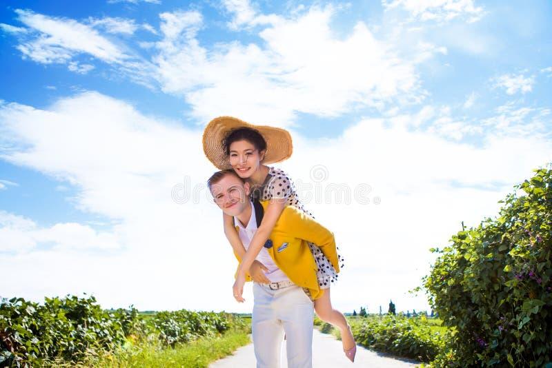 Download Stående Av Den Lyckliga Mannen Som Piggybacking Kvinnan På Vandringsledet Under Fält Mot Molnig Himmel Fotografering för Bildbyråer - Bild av älska, intygar: 78732111