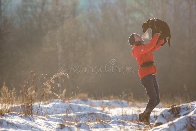 Stående av den lyckliga mannen som rymmer hans vänhund på den soliga ängen i vinter royaltyfria foton