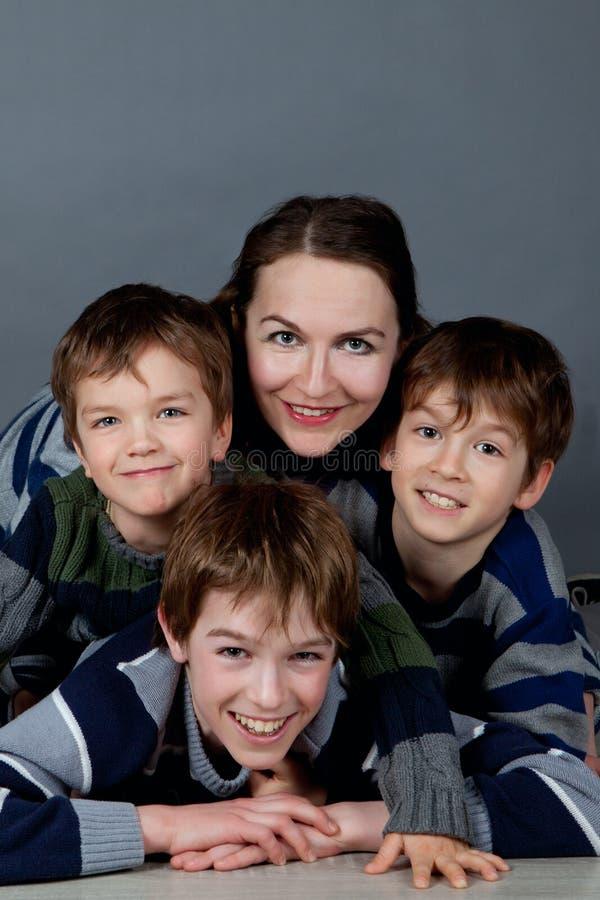 Stående av den lyckliga modern och tre söner, studio arkivfoton