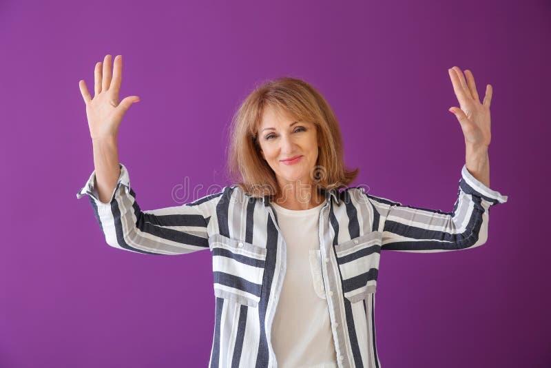 Stående av den lyckliga mogna kvinnan med lyftta händer på färgbakgrund royaltyfri fotografi